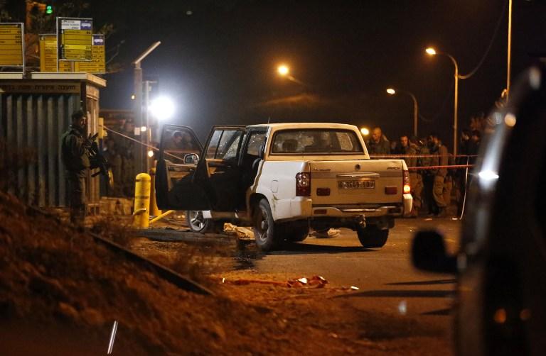 La police scientifique et les forces de sécurité israéliennes sur le site d'une tentative d'attaque à la voiture bélier près de l'implantation d'Adam, à l'est de Ramallah, en Cisjordanie, le 25 janvier 2017. (Crédit : Ahmad Gharabli/AFP)