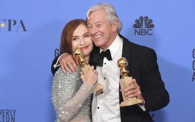 """Isabelle Huppert, lauréate du Golden Globes de la meilleure actrice pour son rôle dans """"Elle"""", du réalisateur Paul Verhoeven, à gauche, qui a remporté le Golden Globe du meilleur film en langue étrangère, à Beverly Hills, le 8 janvier 2017. (Crédit : Kevin Winter/Getty Images/AFP)"""