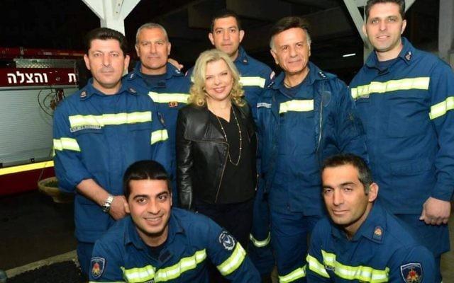Un pompier chypriote, à droite de Sara Netanyahu, l'épouse du Premier ministre, porte une veste de chef inspecteur avec trois étoiles, alors qu'il ne serait qu'inspecteur (deux étoiles), en novembre 2016. (Crédit : Kobi Gidon/GPO)