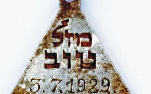 """Un pendentif portant les mots hébreux """"mazal tov"""" et la date du 3 juillet 1929 retrouvé dans le camp d'extermination de Sobibor. (Crédit : Yoram Haimi/Autorité israélienne des antiquités)"""