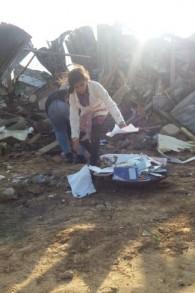 Une fille ramasse ce qui semble être des manuels scolaires et des cahiers d'école dans les décombres de sa maison à Umm al-Hiran le 18 janvier 2017 (Crédit: Dov Lieber / Times of Israel)