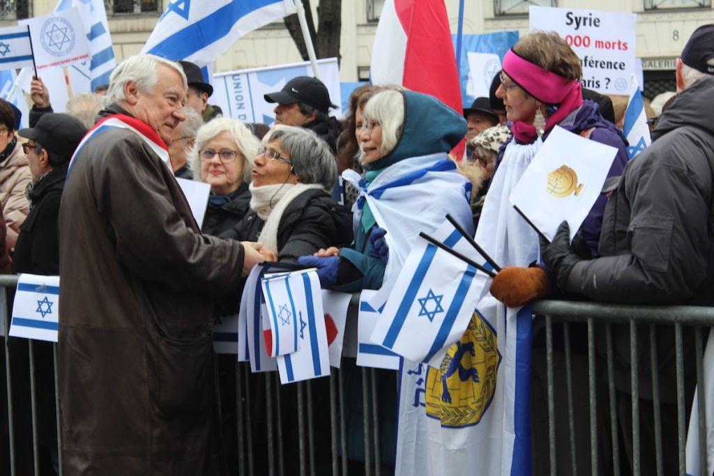 Claude Goasguen, député-maire de Paris connu pour son engagement en faveur d'Israël, salue la foule. (Crédit : Glenn Cloarec/Times of Israël)