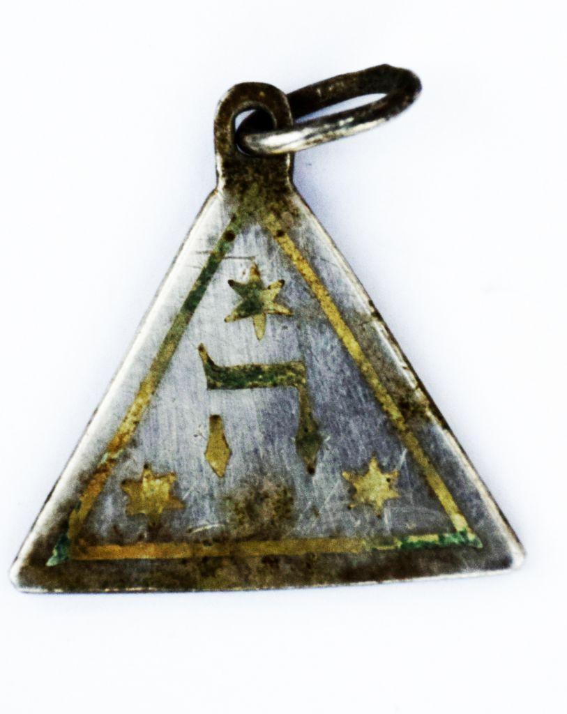 """L'autre face d'un pendentif portant les mots hébreux """"mazal tov"""" et la date du 3 juillet 1929 retrouvé dans le camp d'extermination de Sobibor. (Crédit : Yoram Haimi/Autorité israélienne des antiquités)"""