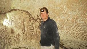 Le spéléologue Ido Meroz à proximité des gravures que lui et ses collègues ont découvert dans un réservoir d'eau des plaines de Judée en décembre 2016 (Crédit : Mickey Barkal via Autorité des Antiquités israélienne )