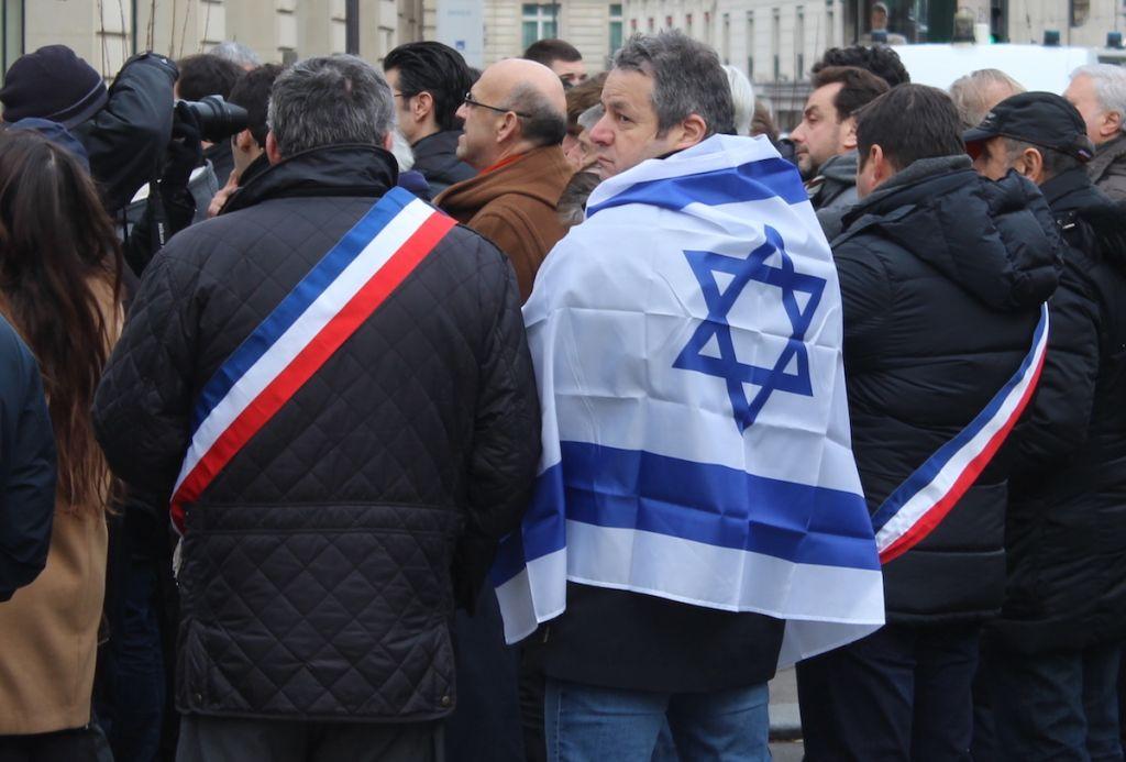 Des élus français et un manifestant, devant la scène de la manifestation contre la conférence de paix à Paris (Crédit : Glenn Cloarec/Times of Israël)