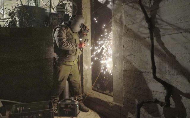 Un soldat israélien ferme un atelier soupçonné d'être utilisé par le Hamas pour fabriquer des armes, à Hébron, le 30 janvier 2017. (Crédit : unité des porte-paroles de l'armée israélienne)