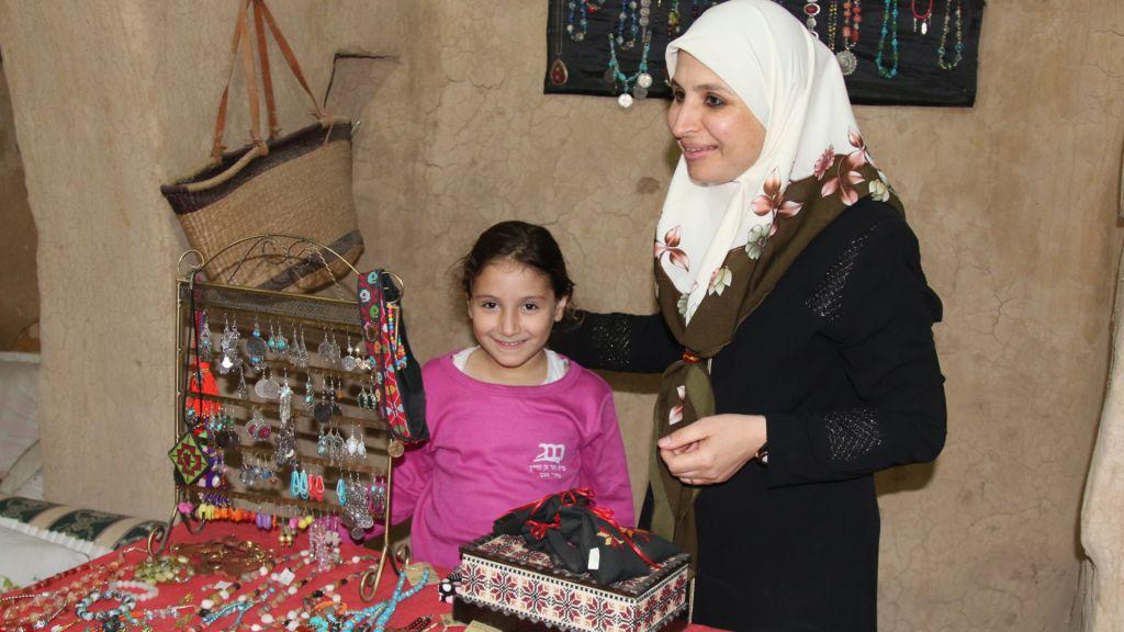 Amal Abu Karen avec sa fille devant certains objets artisanaux produits par les artisans du village  (Crédit : Shmuel Bar-Am)