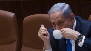 Le Premier ministre israélien Benjamin Netanyahu boit un café durant la séance plénière de l'assemblée du Parlement israélien, le 17 juin 2015.  (Crédit : Miriam Alster/FLASH90)