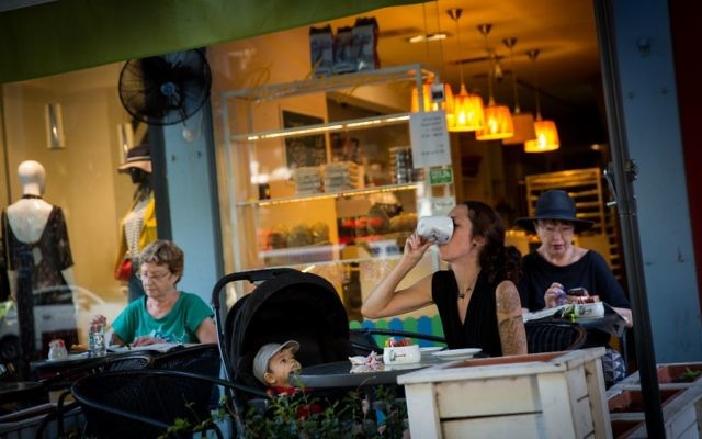 Des Israéliens boivent un café en terrasse d'un bar, rue Dizengoff à Tel Aviv le 3 octobre 2016 (Crédit :   Miriam Alster/FLASH90)