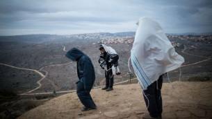 Des Juifs priant tôt le matin sur la colline surplombant Ofra dans l'avant-poste juif d'Amona en Cisjordanie, le 18 décembre 2016 (Crédit : Miriam Alster / Flash90)
