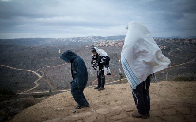 Des Juifs priant tôt le matin sur la colline surplombant Ofra, dans l'avant-poste d'Amona en Cisjordanie, le 18 décembre 2016. (Crédit : Miriam Alster/Flash90)