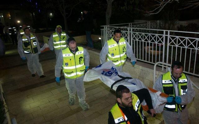 Les bénévoles de ZAKA portent les corps d'une femme et de ses quatre enfants, à Jérusalem, le 1er janvier 2017. (Crédit : Yonatan Sindel/Flash90)