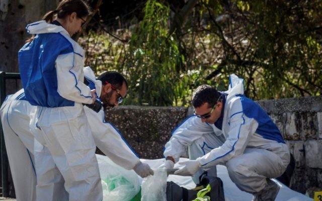 Des médecins légistes enquêtent sur le lieu où un homme a été assassiné après qu'un tireur inconnu ait ouvert le feu, faisant un mort, à Haifa, le 3 janvier 2017 (Crédit : Meir Vaknin/Flash90)