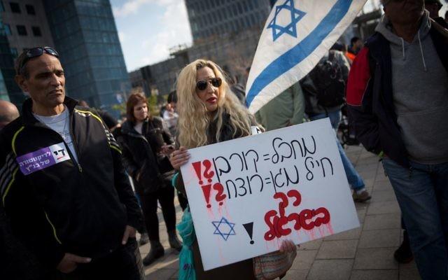 """Des soutiens d'Elor Azaria, jugé coupable d'homicide, avec un panneau """"terroriste = victime ?! soldat protecteur = assassin ?!"""" devant la cour militaire de la Kirya à Tel Aviv, le 4 janvier 2017. (Crédit : Miriam Alster/Flash90)"""