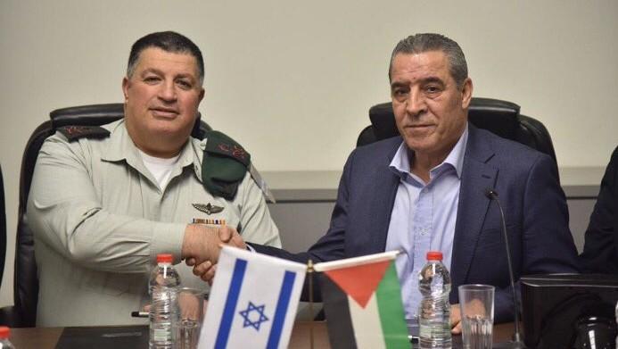 Yoav Mordechai, dirigeant du COGAT, et Hussein al-Sheikh, ministre des Affaires civiles de l'Autorité palestinienne, après la signature d'un accord de coopération sur l'eau, le 15 janvier 2017. (Crédit : COGAT)