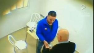 Le député Basel Ghattas remettrait un paquet au prisonnier palestinien Walid Daka dans une vidéo diffusée le 23 janvier 2017. (Crédit : capture d'écran Deuxième chaîne)