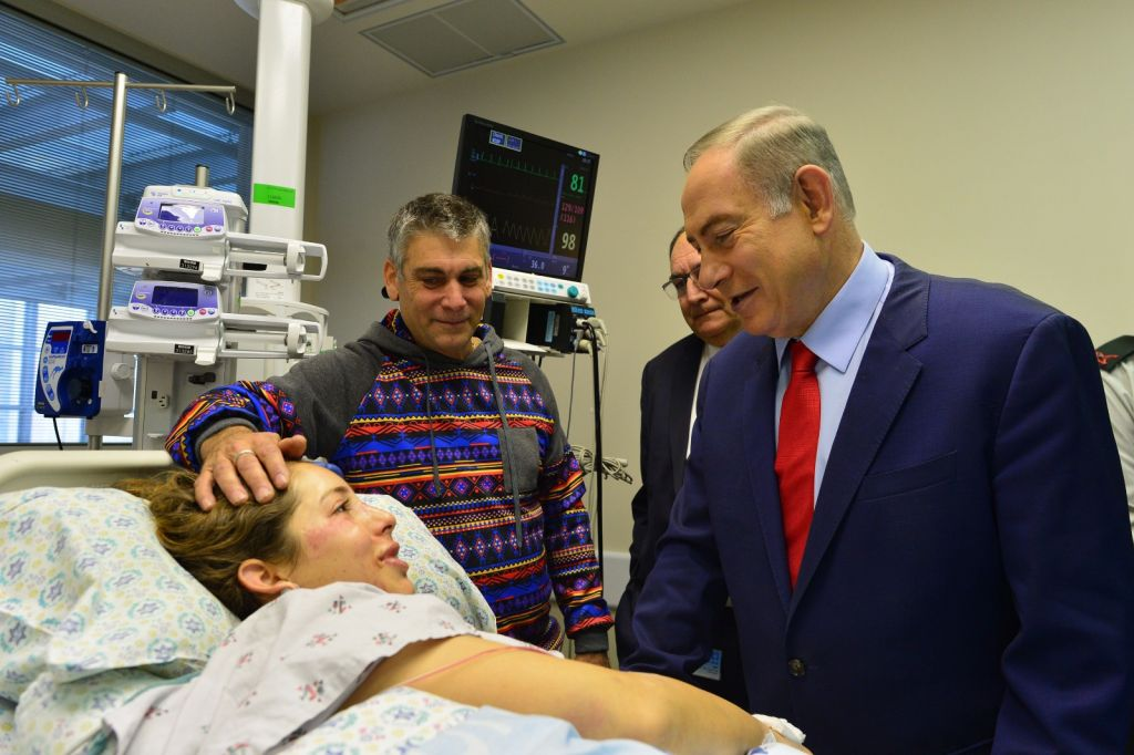 Le Premier ministre Benjamin Netanyahu au chevet d'une victime de l'attentat terroriste au camion bélier du 8 janvier à Jérusalem, qui a fait quatre morts et 16 blessés, le 9 janvier 2017. (Crédit : Kobi Gideon/GPO)