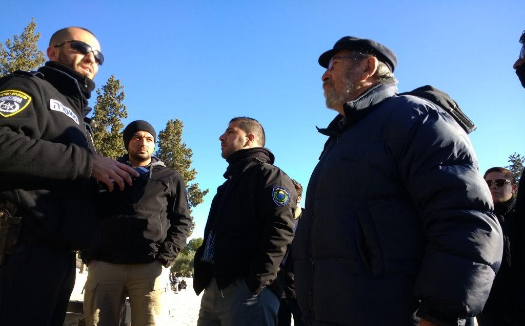 L'archéologue Gabriel Barkay, à droite, encadré par les gardes du Waqf, devant la police israélienne, sur le mont du Temple, le 1er janvier 2017. (Crédit : Ilan Ben Zion/Times of Israël)