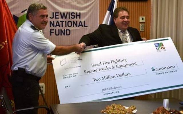 Le commandant des pompiers Shimon Ben Ner reçoit un don de Russel Robinson, président du KKL américain. (Crédit: Dennis Zinn/KKL)