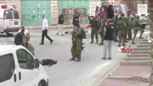 Un soldat de l'armée israélienne charge son arme avant qu'il ne paraisse tirer sur un Palestinien désarmé et blessé qu'il atteindra à la tête, après une attaque au couteau perpétrée le 24 mars 2016 à Hébron. ((Capture d'écran : : B'Tselem)
