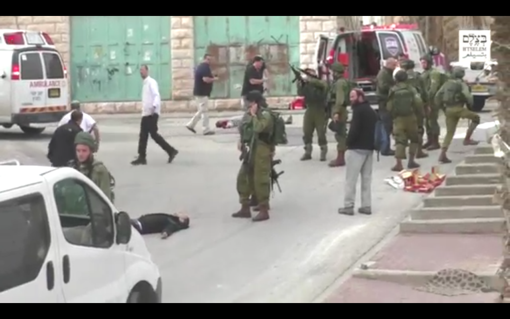 Un soldat de l'armée israélienne charge son arme avant qu'il ne paraisse tirer sur un Palestinien désarmé et blessé qu'il atteindra à la tête, après une attaque au couteau perpétrée le 24 mars 2016 à Hébron. (Crédit : capture d'écran : : B'Tselem)
