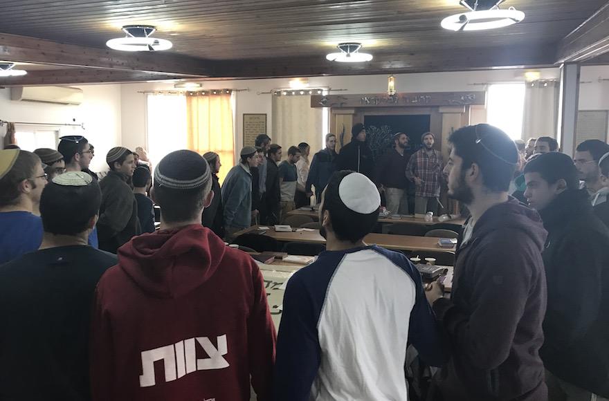 Jeunes hommes dansant et chantant dans la synagogue d'Amona, le 13 décembre 2016. (Crédit : Andrew Tobin/JTA)