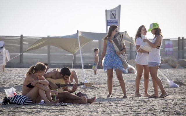 Des Israéliens profitent du temps doux sur la page de Tel Aviv le 3 octobre 2016 (Crédit :  Nati Shohat/FLASH90)