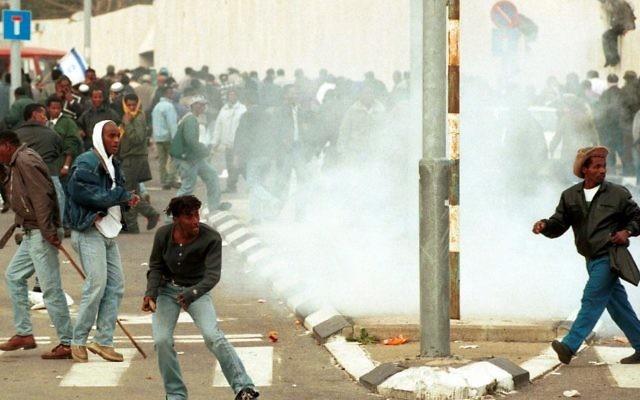 """Affrontements violents entre la police et des Israéliens éthiopiens,  qui manifestent pour protester contre ce qu'ils perçoivent être un statut de """"citoyen de seconde classe"""" de la part du gouvernement. La manifestation avait commencé lorsque l'opinion publique avait appris que le sang donné par les Ethiopiens dans les hôpitaux et dans centres de don du sang mobiles était jeté, en raison de craintes d'infection au VIH. Le 28 janvier 1996 . (Crédit : Flash90)"""