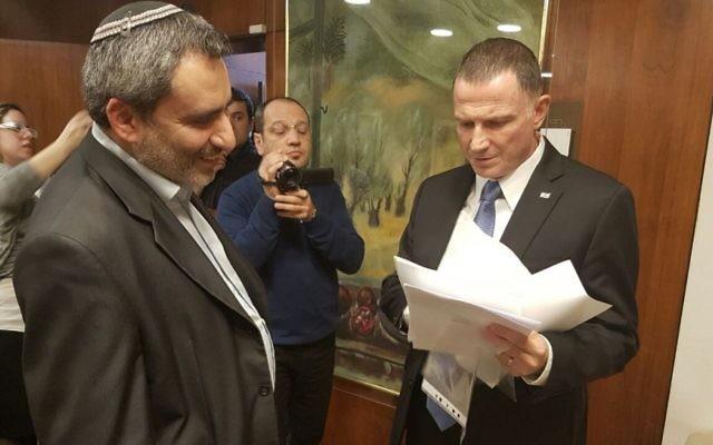 Yuli Edelstein, à droite, président de la Knesset, avec les 72 signatures de député demandant un vote sur la destitution du député arabe Basel Ghattas, remises par Zeev Elkin, à gauche, ministre du Likud, à la Knesset, le 16 janvier 2017. (Crédit : département des portes-paroles de la Knesset)
