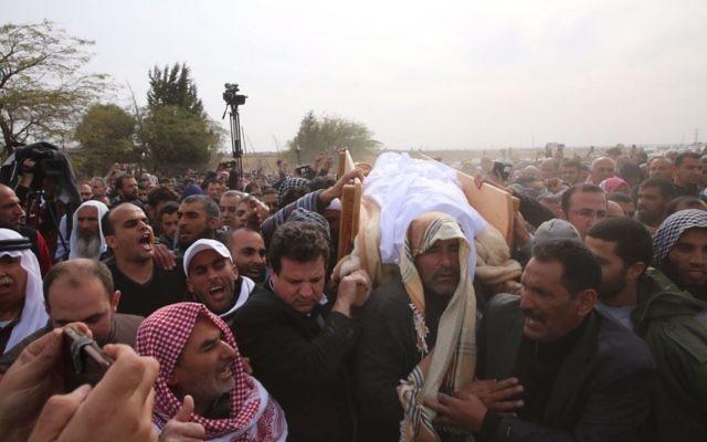 Le leader de la liste arabe unie, le député Ayman Odeh portant la dépouille de Yaqoub Mousa Abu Al-Qia'an (Crédit : Autorisation)