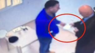 Des extraits de caméras de surveillance montrent Basel Ghattas, à droite, remettre une enveloppe à un détenu dans une prison israélienne. (Crédit : capture d'écran de la Dixième chaine)