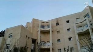 Traces de feu visibles à la fenêtre d'un appartement de la route de Hébron où ont été retrouvés les corps d'une femme et de ses quatre enfants, à Jérusalem, le 1er janvier 2017. (Crédit : capture d'écran Deuxième chaîne)