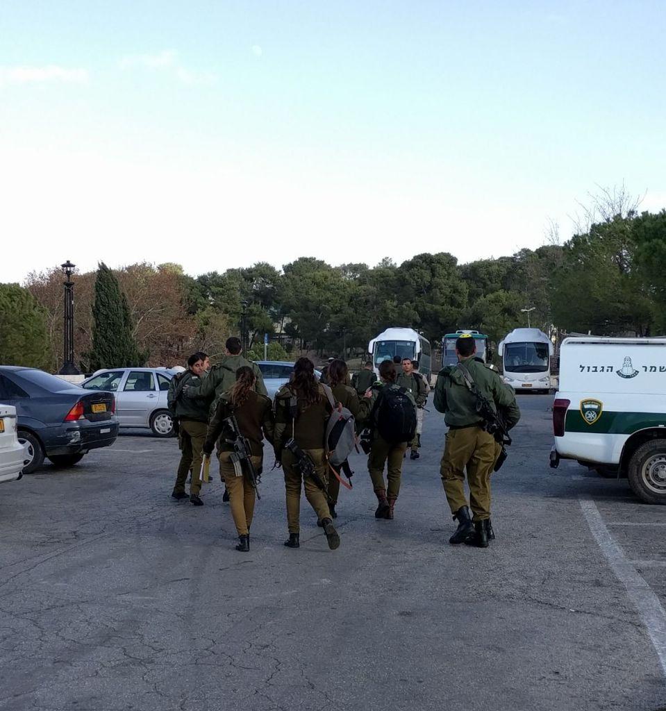 """Des soldats quittent la scène d'un attentat au camion bélier qui a fait quatre morts et plus de dix blessés, à Jérusalem, le 8 janvier 2017. Beaucoup pleurent, les commandants ne cessent de crier """"ne regardez pas, ne regardez pas"""". (Crédit : Melanie Lidman/Times of Israël)"""