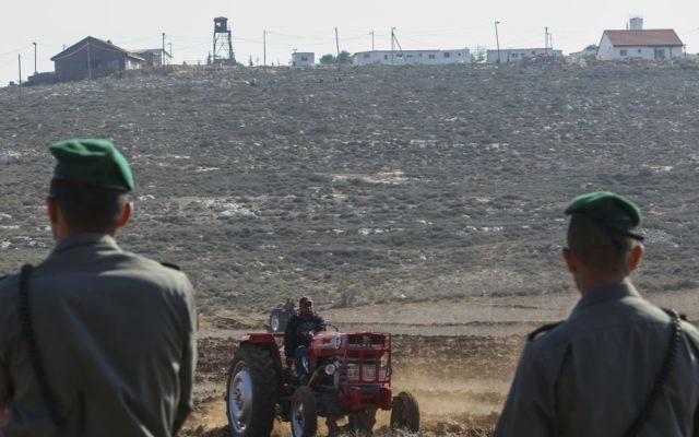 Les officiers de la police des frontières montant la garde pendant que les agriculteurs palestiniens utilisent des tracteurs pour travailler la terre dans le village de Qusra en Cisjordanie, avec l'avant-poste Esh Kodesh en arrière-plan, le 19 novembre 2013. (Crédit : Nati Shohat/Flash90)