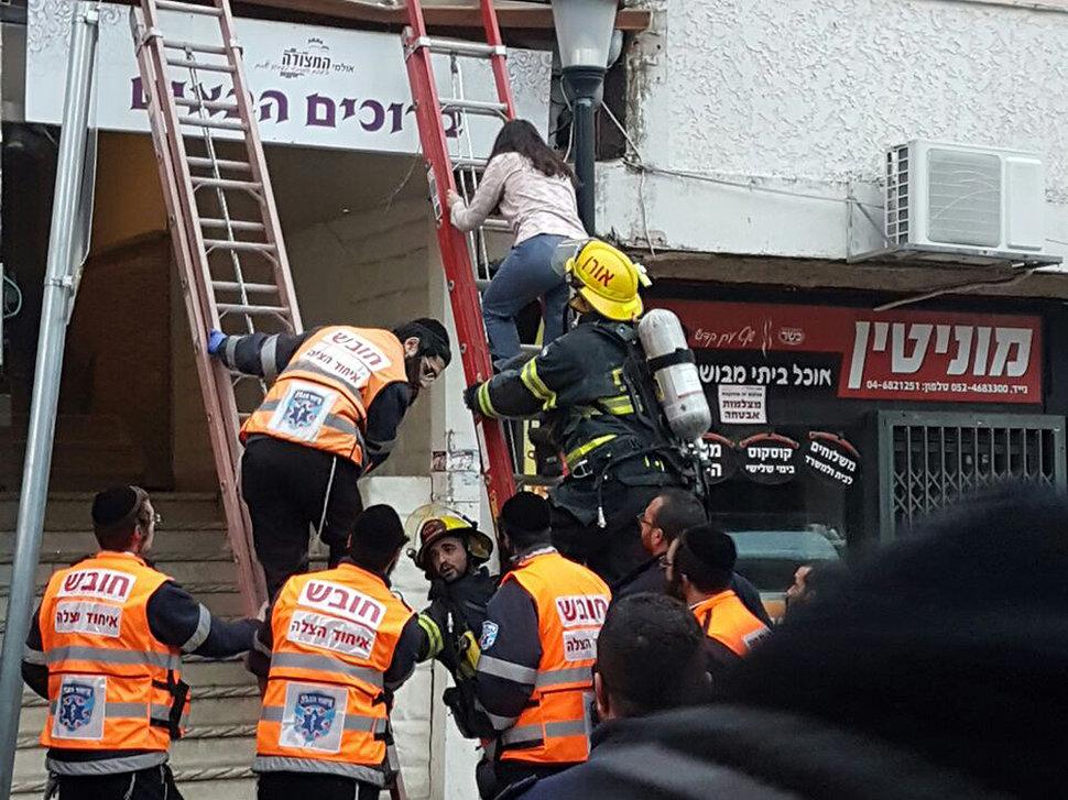 Evacuation des clients d'un hôtel de Safed, dans le nord du pays, en raison d'un incendie qui a fait 16 blessés dont deux graves, le 8 janvier 2016. (Crédit : pompiers israéliens)