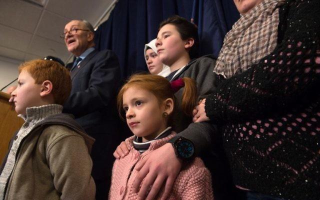 Le sénateur américain Chuck Schumer , ici avec des réfugiés, œuvre pour annuler le décret de Trump, interdisant temporairement l'immigration aux États-Unis de réfugiés et des certains voyageurs musulmans, lors d'un conférence de presse le 29 janvier 2017. (Crédit : AFP PHOTO/ Bryan R. Smith)