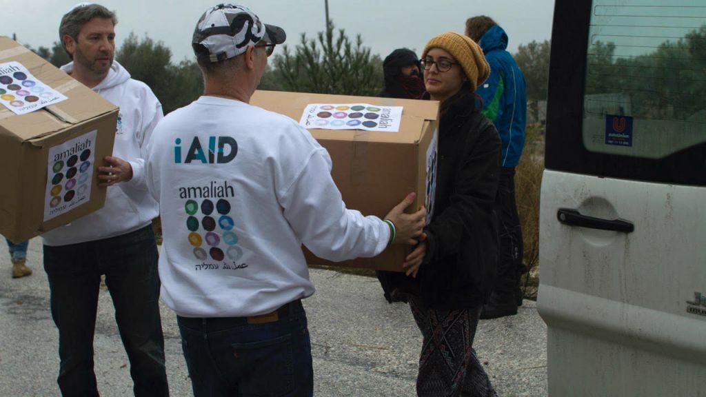 Le rabbin Shu Eliovson (à gauche) et Moti Kahana (au centre) déchargeant les vivres et les vêtements collectés en Israël pour les réfugiés avec Molly Nixon de Lifting Hands International à Lesbos, en Grèce, le 19 janvier 2017 (Crédit : Nave Antopolsky / iAID)
