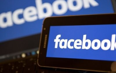 Une photo prise le 21 novembre 2016 montrant des logos Facebook sur les écrans d'un smartphone (à droite) et sur un ordinateur portable, dans le centre de Londres (Crédit : AFP)