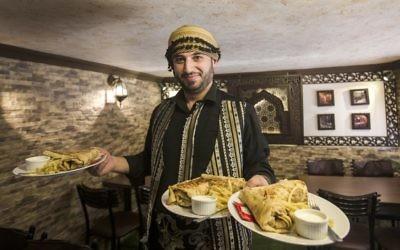 Anas Qaterji, un réfugié syrien qui a fui la guerre à Alep, en train de servir de la nourriture dans son restaurant dans le camp de réfugiés de Nuseirat, dans le centre de la bande de Gaza, le 3 janvier 2017 (Crédit : AFP PHOTO / MAHMUD HAMS)