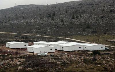 Construction de nouvelles maisons préfabriquées en Cisjordanie, entre l'avant-poste d'Amona (au fond) et l'implantation d'Ofra, au nord de Ramallah, le 31 janvier 2017. (Crédit : Thomas Coex/AFP)