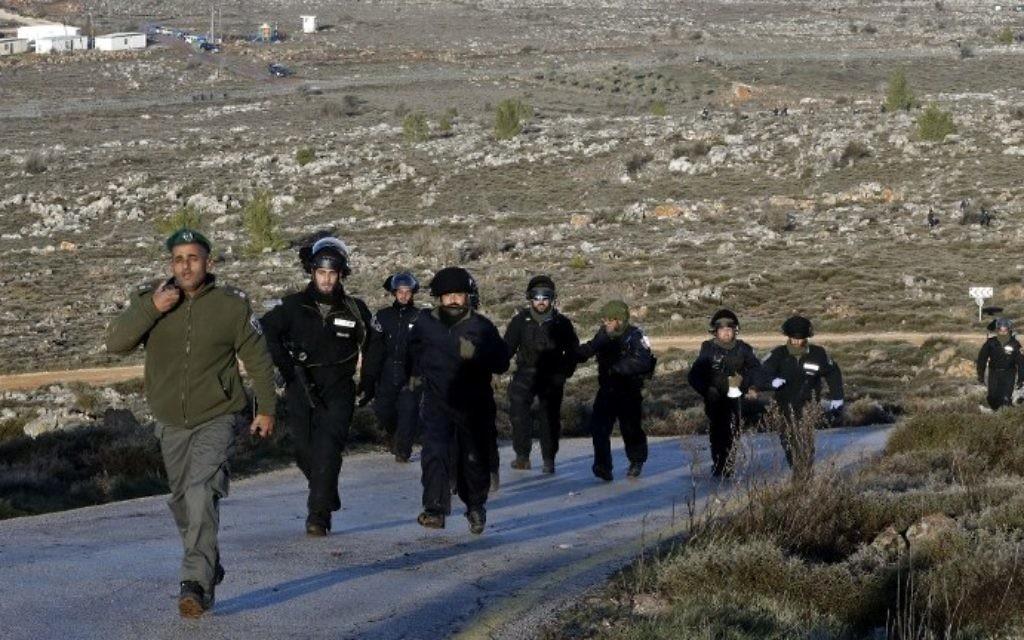 Les forces de sécurité israéliennes se rassemblent à l'avant-poste d'Amona, au nord est de Ramallah, en Cisjordanie, le 1er février 2017. (Crédit : Jack Guez/AFP)