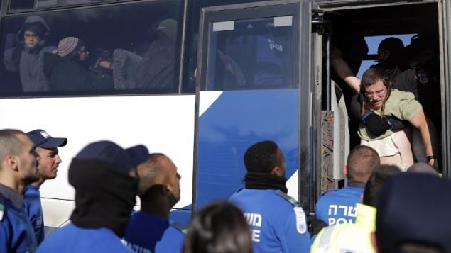 La police israélienne en train de mettre un résident d'une implantation dans un autobus après avoir été expulsé de l'avant-poste de l'implantation d'Amona le deuxième jour d'une opération de police israélienne pour évacuer l'avant-poste, le 2 février 2017, (Crédit : AFP PHOTO / Thomas COEX)