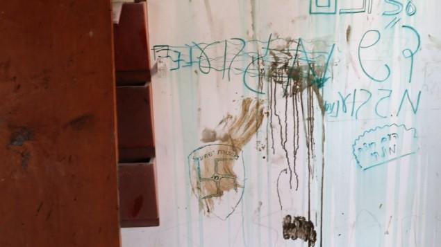 Les graffitis et la croix gammées sur le mur de la synagogue d'Amona après que des jeunes se soient barricadés avant d'être expulsés le 2 février 2017 (Crédit : AFP PHOTO / Thomas COEX)