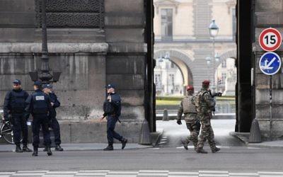 Des policiers et des soldats français patrouillent suite à une attaque devant le musée du Louvre, à Paris, le 3 février 2017. (Crédit : Alain Jocard/AFP)