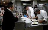 """Lors de l'édition 2017, le chef français Laurent Delarbre (au centre) aide à préparer un menu casher, sous la supervision d'un rabbin (à gauche), lors de la semaine consacrée à la cuisine française, """"So French, so Food au restaurant """"La Vache sur le toit"""""""", le 8 février 2017 à Jérusalem (Crédit : AFP PHOTO / THOMAS COEX)"""