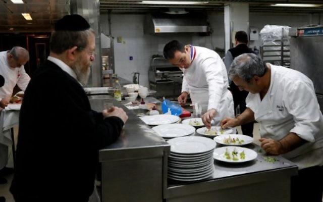 """Lors de la derinère édition, le chef français Laurent Delarbre (au centre) aide à préparer un menu casher, sous la supervision d'un rabbin (à gauche), lors de la semaine consacrée à la cuisine française, """"So French, so Food au restaurant """"La Vache sur le toit"""""""", le 8 février 2017 à Jérusalem (Crédit : AFP PHOTO / THOMAS COEX)"""
