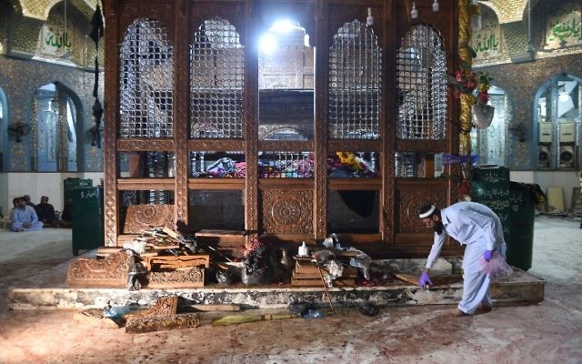 Un responsable pakistanais rassemble des preuves au lendemain d''une attaque à la bombe qui a frappé le sanctuaire soufi musulman Lal Shahbaz Qalandar dans la ville de Sehwan dans la province de Sindh, à environ 200 kilomètres au nord-est de la capitale Karachi, le 17 février 2017 (AFP PHOTO / ASIF HASSAN)