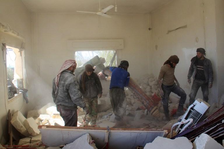 Les membres de la défense civile syrienne inspectent la maison du jeune Abdel Basset al-Stouf, dans la ville d'Al-Hbeit, le 17 février 2017. (Crédit :  AFP PHOTO / Omar haj kadour)