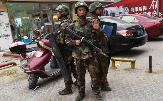 """Policiers des forces spéciales déployés devant le centre commercial de Hotan, dans la région chinoise de Xinjiang, en proie à des tensions entre les Hans et les Ouïghours musulmans, dans le cadre de la campagne """"anti-terroriste"""", le 16 avril 2015. (Crédit : Greg Baker/AFP)"""
