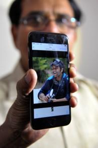 Jagan Mohan Reddy montre la photographie de son fils, Alok Madasani, tué au Kansas le 22 février 2017. (Crédit : Noah Seelam/AFP)